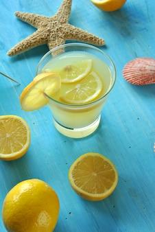 Limonada fresca com estrela do mar e conchas na mesa azul