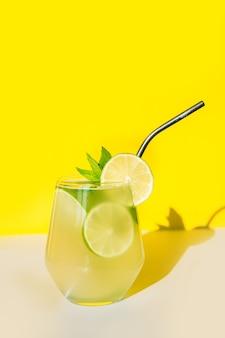 Limonada fresca de verão com limão, limão, laranja e hortelã em fundo amarelo