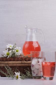 Limonada fresca em vidro e frasco com margaridas na mesa branca.
