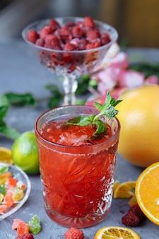 Limonada fresca rosa com framboesas decorada com folhas de hortelã, limão, laranja e frutas cristalizadas