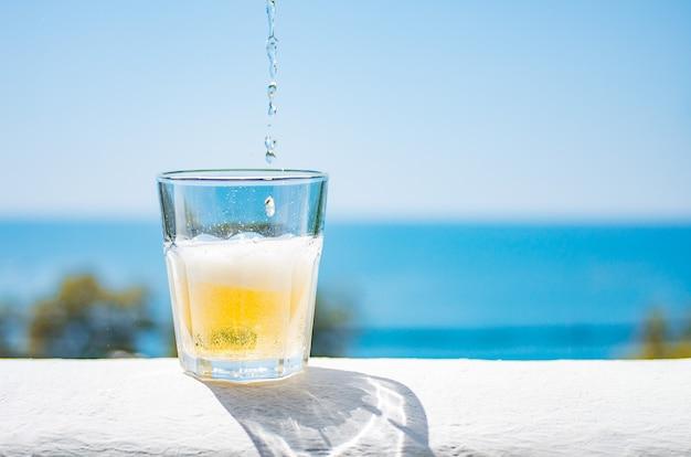 Limonada gelada é despejada em um copo.um copo de limonada refrescante contra o pano de fundo o