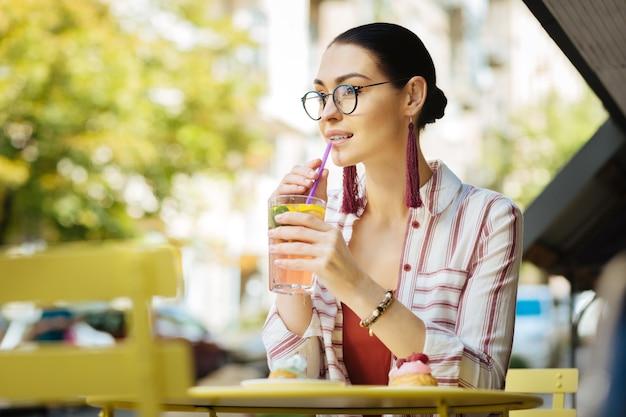 Limonada gelada. linda pessoa relaxada visitando um café de rua e usando um canudinho enquanto bebe uma limonada gelada