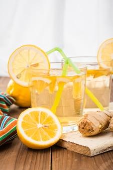 Limonada, limões e gengibre em uma mesa de madeira