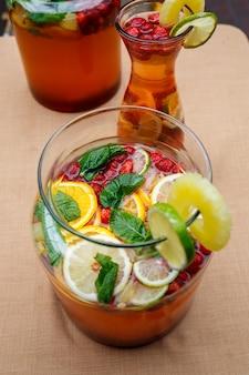 Limonada refrescante com frutas frescas, laranja, limão, cereja e folhas de hortelã. delicioso coquetel de frutas sem álcool em uma jarra