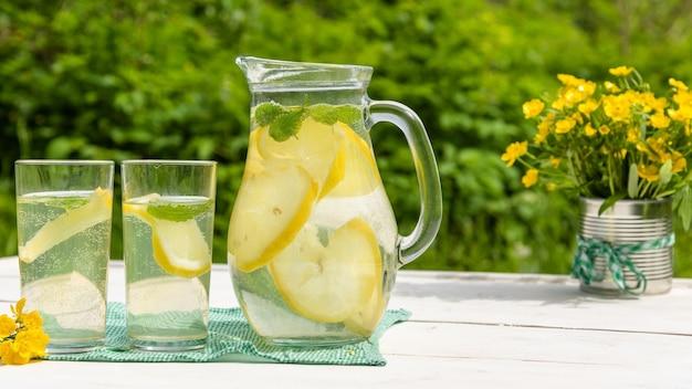 Limonada refrescante com rodelas de limão na natureza.