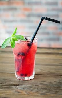 Limonada refrescante vermelha com bagas e gelo em uma mesa de madeira. bebida de verão.