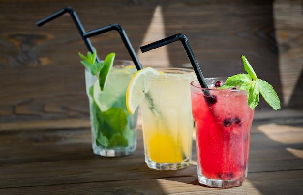 Limonada três refrescante diferente com limão e limão em uma mesa de madeira. bebida de verão