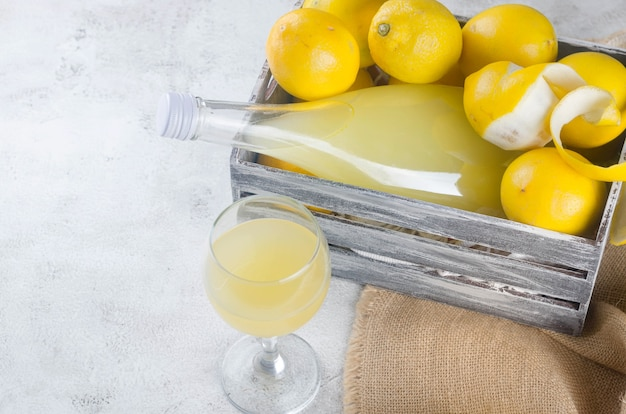 Limoncello em garrafa de vidro e limões amarelos maduros frescos no fundo cinza, licor de limão italiano doce caseiro tradicional, bebida alcoólica forte e limões amarelos maduros frescos.