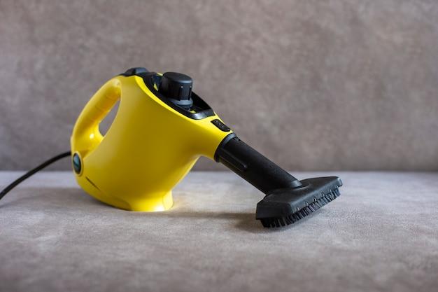Limpador a vapor amarelo com escova em um sofá marrom