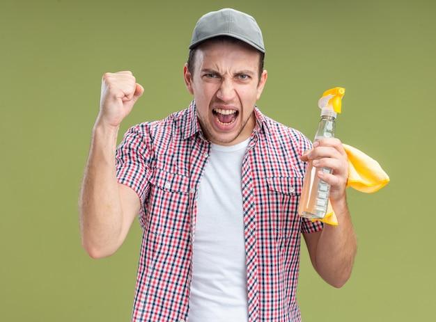 Limpador de cara jovem animado usando boné segurando agente de limpeza com pano mostrando gesto de sim isolado na parede verde oliva