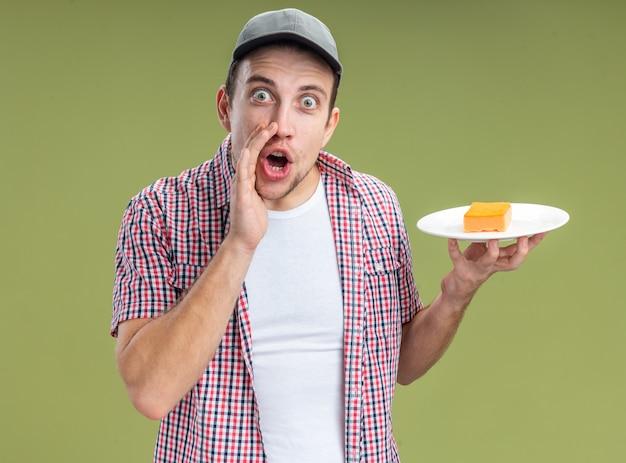 Limpador de cara jovem animado usando boné, segurando uma esponja no prato, chamando alguém isolado na parede verde oliva