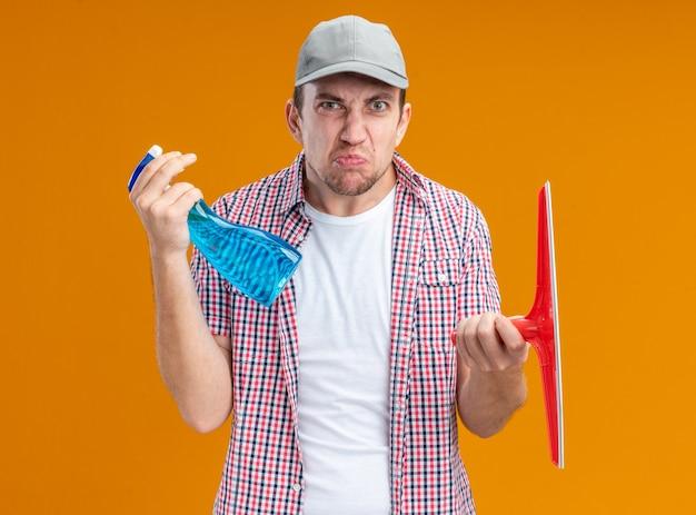 Limpador de cara jovem descontente com boné segurando agente de limpeza com a cabeça do esfregão isolada em fundo laranja