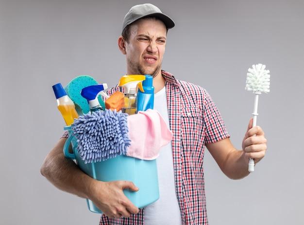 Limpador de cara jovem enjoado usando boné, segurando um balde com ferramentas de limpeza e olhando para a escova na mão, isolado no fundo branco