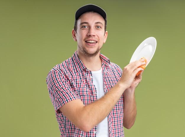 Limpador de cara jovem sorridente usando boné lavando prato com esponja isolada na parede verde oliva