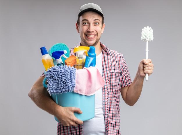 Limpador de cara jovem sorridente usando boné segurando um balde com escova de ferramentas de limpeza isolada no fundo branco