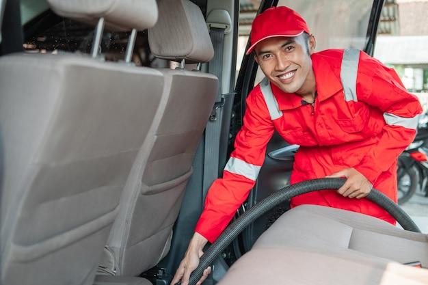 Limpador de carro masculino usa uniforme sorridente vermelho enquanto limpa o chão do carro com aspirador de pó no carro
