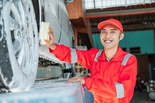 Limpador de carro masculino usa uniforme vermelho e chapéu sorridente enquanto lava a parte inferior do carro no salão automotivo