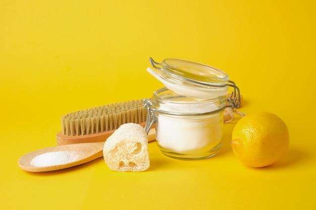 Limpador de lixo zero, lata de refrigerante, escova de madeira, limão, ácido cítrico e bucha em fundo amarelo