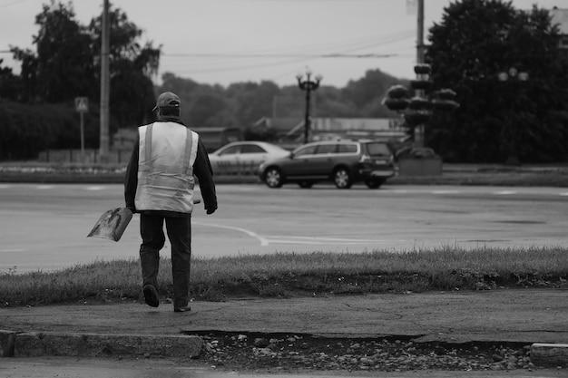 Limpador de rua vai trabalhar na rua no início da manhã. o trabalhador vai em direção à estrada.