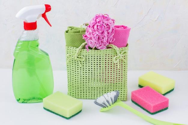 Limpador de vidro, esponja, escova e toalhas e flores na sacola