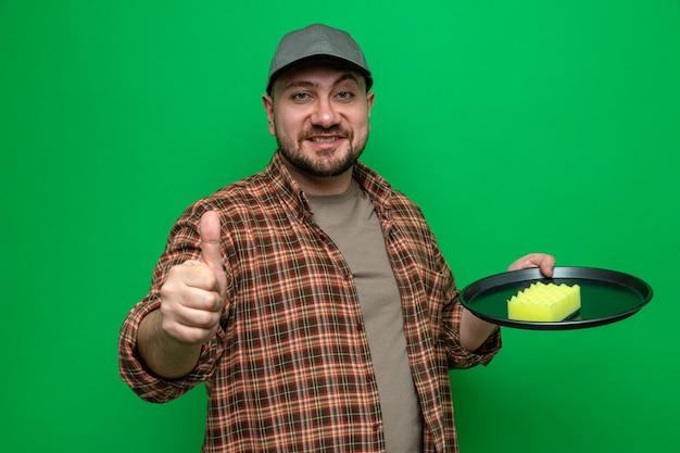 Limpador eslavo sorridente, limpando pratos com uma esponja e apontando para cima