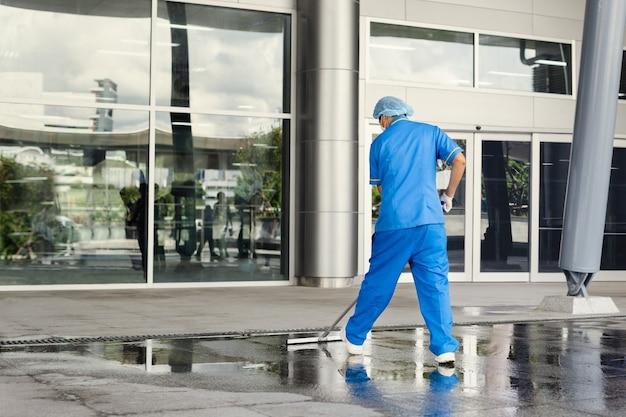 Limpador industrial profissional em piso de limpeza de proteção uniforme