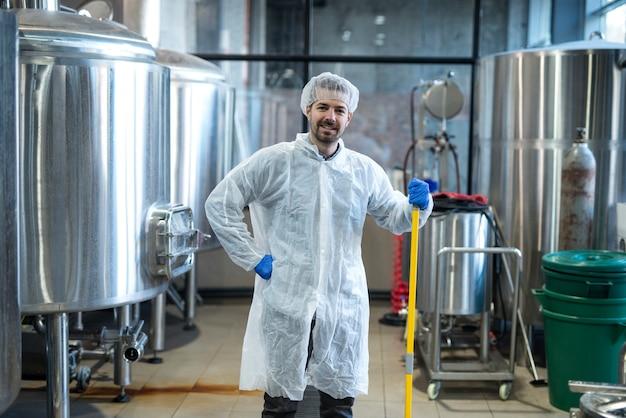 Limpador industrial profissional em traje de proteção segurando um esfregão de microfibra