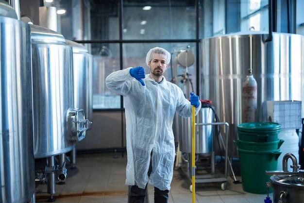 Limpador industrial profissional em uniforme de proteção segurando os polegares para baixo