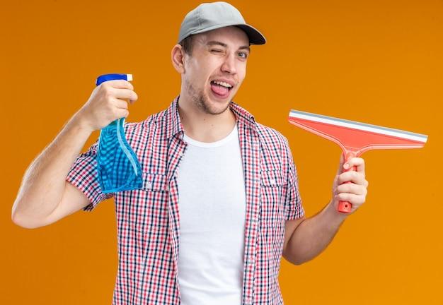 Limpador jovem alegre e piscando usando boné segurando o agente de limpeza com esfregão mostrando a cabeça da língua isolada em fundo laranja