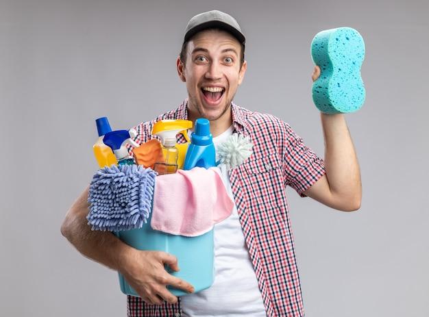 Limpador jovem animado usando boné, segurando um balde com ferramentas de limpeza e uma esponja de limpeza isolada no fundo branco