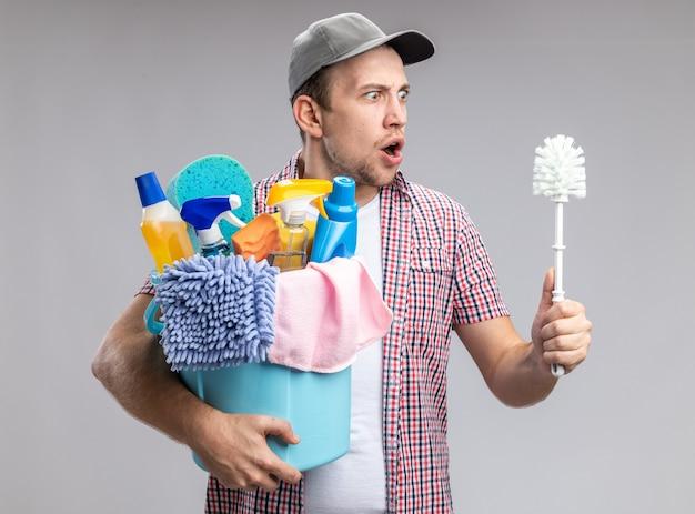 Limpador jovem assustado usando boné, segurando um balde com ferramentas de limpeza e olhando para a escova na mão, isolado no fundo branco