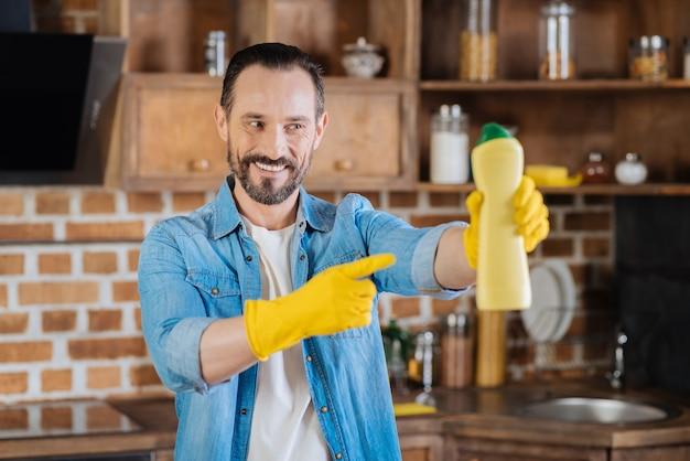 Limpador masculino alegre e alegre apresentando limpador enquanto olha para ele e sorri