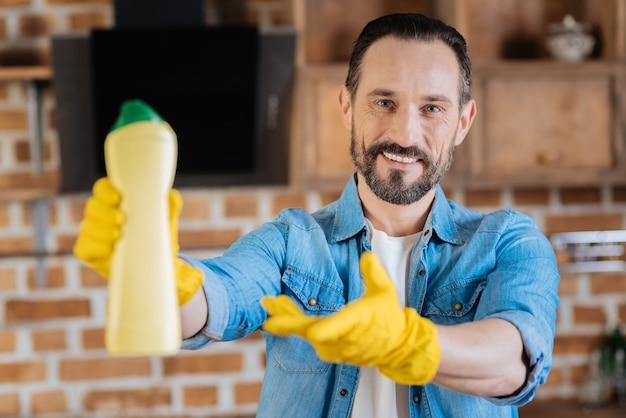 Limpador masculino alegre e alegre recomendando um limpador enquanto estica a mão e sorri para a câmera