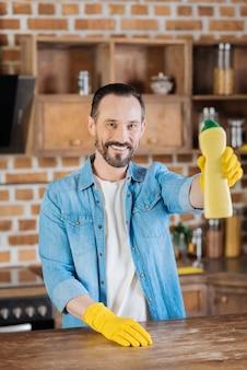 Limpador masculino positivo e alegre propondo limpador enquanto coloca a mão na superfície e sorri para a câmera