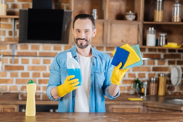 Limpador masculino vigoroso e feliz segurando meios de limpeza enquanto sorri e se veste com luvas