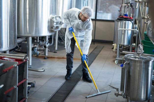 Limpador profissional usando proteção uniforme de limpeza de piso da fábrica