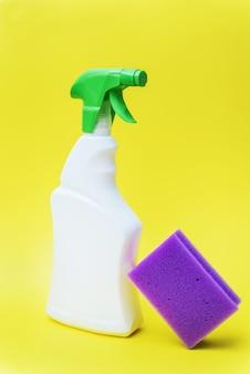 Limpador químico em spray e esponja roxa em fundo amarelo