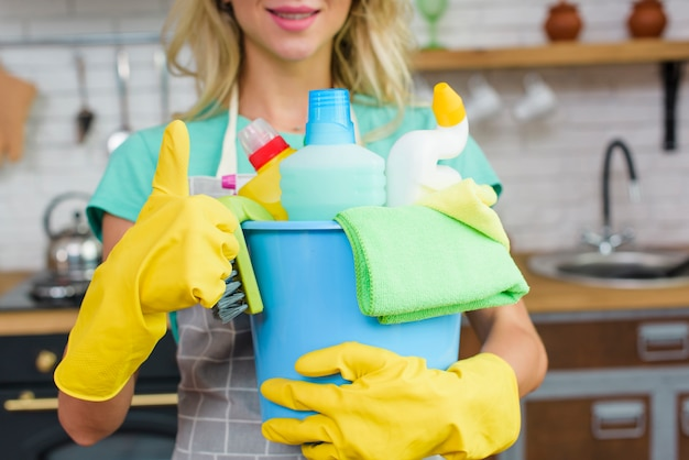 Limpador segurando ferramentas de limpeza e produtos mostrando o gesto de thumbup