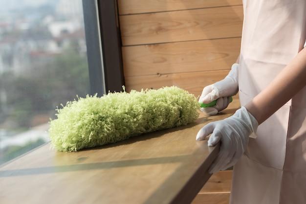 Limpadora de mulher limpando mesa com espanador