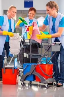 Limpadores comerciais fazendo o trabalho juntos, três mulheres com um carrinho trabalhando