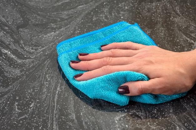 Limpando a bancada. cuidar de bancadas na cozinha ou no banheiro. limpeza de bancadas em pedra, mármore ou pedra artificial. a mão da mulher limpa a superfície da bancada de mármore.