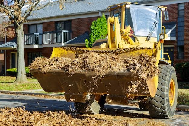 Limpando a cidade durante o outono, folhas de outono caídas da estrada e da calçada com um trator