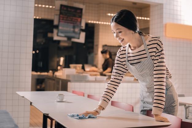 Limpando a mesa. garçonete profissional de cabelos escuros diligente limpando a mesa pela manhã