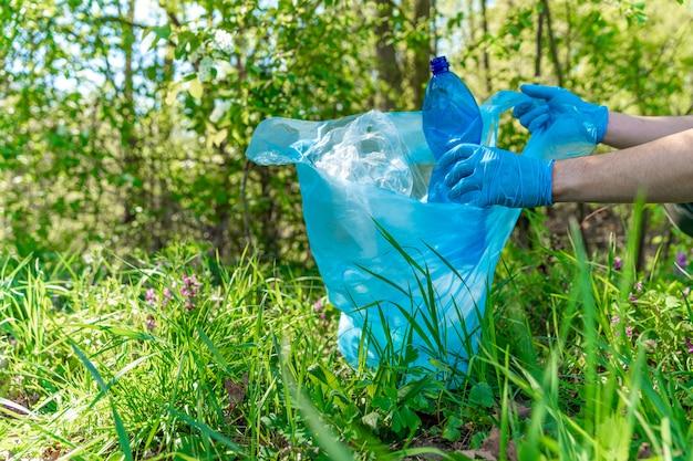 Limpando a natureza coletando resíduos plásticos, as garrafas plásticas da bebida causam um desastre ecológico
