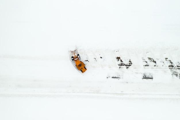 Limpando a neve das ruas após uma forte nevasca. o trator limpa a visão da neve do topo.