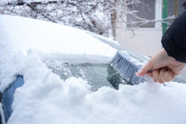 Limpando a neve do pára-brisa do carro com a escova do carro