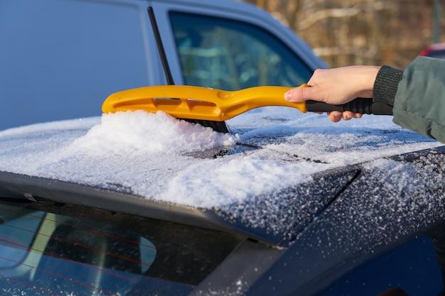 Limpando a neve do teto de um carro com uma escova