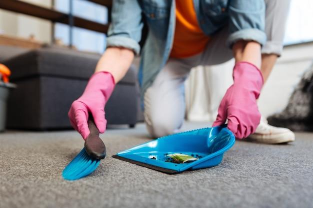Limpando a sujeira. limpadora trabalhadora usando luvas de proteção cor de rosa e roupas confortáveis enquanto lida com a limpeza do chão