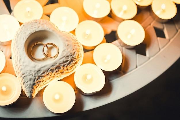 Limpando anéis em um castiçal de porcelana em forma de coração, e velas estão acesas ao redor