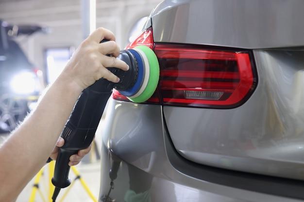 Limpando as luzes traseiras do carro a partir de arranhões com máquina de polir, polindo arranhões em um carro
